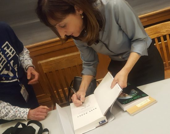 "Jane Mayer signs her book ""Dark Money"" for a fan on top of her copy of ""The Bonobo Way."""