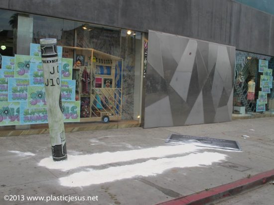 One of LA's most fashionable shopping districts was hit over night by a giant cocaine themed art installation.. The 12 foot long lines of cocaine and 7 foot high $100 bill, along with a platinum American Express card - renamed 'American Excess' jas proved quite a tourist attraction. With passers by stopping their cars to pose for photos. Even two passing cops had to double- take after crusing past the mamoth streetart installation. The nacortic themed piece is beleived to the work of controversial street artist 'Plastic Jesus' who earlier in 2013 painted a piece moking discgraced cyclist Lance Armstrong. The 3 foot wide stencil painted work showed armstring connected to and IV drip.