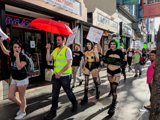 """Bryan and Lexi Lore, holding the """"Sex Work Is Real Work"""" sign, march for International Whores Day. Photo: Jux Lii"""