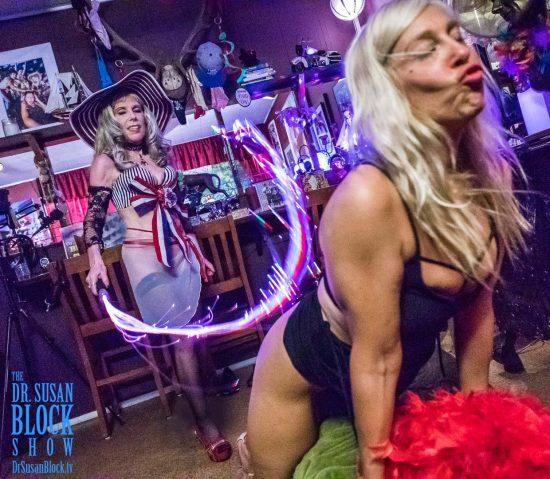Goddess Phoenix's Neon Whip Licks Brigitte's Hot Butt. Photo: Jux Lii