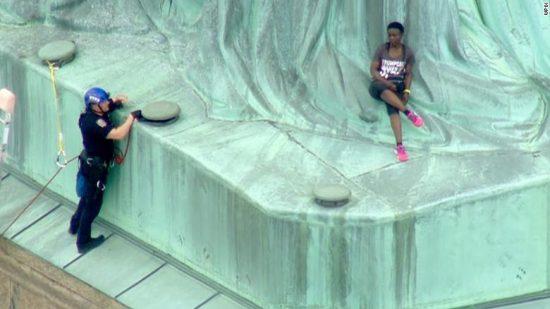 Therese Patricia Okoumou's Statue of Liberty climbing attire: Anti-Trump Tee & Hot Pink Sneaks.