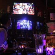 Nori watches from the bar