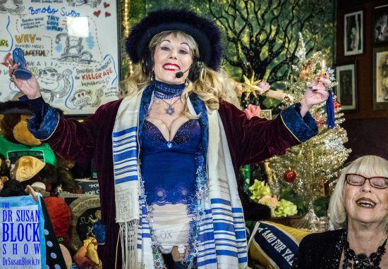"""In My Shtreimel, Tallith, prison-made Star of David and """"LOX et Veritas"""" panties, I hold a flaming Hanukkah candle and the Baby Jesus Buttplug heavenward, with """"Guest Rebbitzen"""" Sheree Rose, thanking all the Gods, Goddesses, Angels & Buttplugs for the """"Mueller Miracle."""" Photo: Jux LiiLii"""